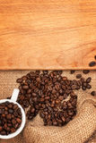 Scattered grains of coffee, cup  and wooden board Stock Image