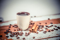 Scattered grains of coffee in a cup on a wooden background Stock Photography
