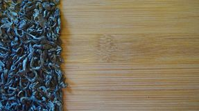 Scattered green tea on wood bamboo background royalty free stock image