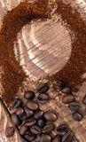 Scattered ground coffee with grains on a wooden table Royalty Free Stock Photography