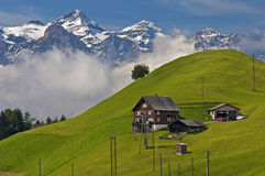 Scattered hamlet in the Prealps. Against the snow-covered peaks of the Swiss Alps, Canton of Uri, Switzerland royalty free stock images