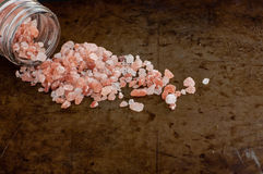 Scattered Himalayan pink salt. Crystals from glass bottle on rusty metal background royalty free stock photography