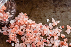 Scattered Himalayan pink salt. Crystals from glass bottle on rusty metal background royalty free stock photos