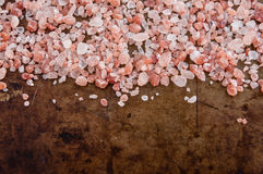 Scattered Himalayan pink salt crystals. Top view on rusty metal background, space for text royalty free stock photos