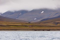 Scattered houses. Isolated buildings on the remote shores of Isfjorden. Svalbard, Spitsbergen, Norway royalty free stock photo