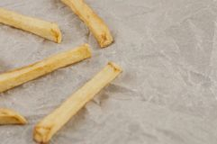 Scattered lot of sticks of french fries on gray crumpled paper. Scattered lot of sticks of tasty french fries on gray crumpled paper royalty free stock images