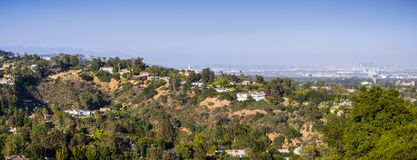 Scattered mansions on one of the hills of Bel Air neighborhood; the downtown skyscrapers visible in the background through a hazy. Atmosphere; Los Angeles royalty free stock photography
