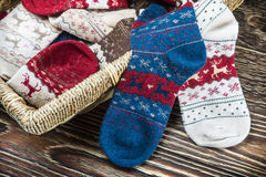 Scattered multi-colored Christmas socks and laundry basket Royalty Free Stock Photo