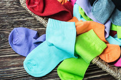 Scattered multi-colored socks and laundry basket Stock Photography
