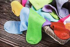 Scattered multi-colored socks and laundry basket Royalty Free Stock Image