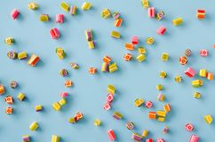 Scattered multicolored sugar candy on a blue background. Blue background with scattered multicolored sugar candy. Toned image royalty free stock photo