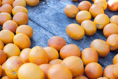 Scattered oranges. A wooden market table with a selection of oranges that have been carelessly scattered over it. The oranges have suffered slight bruising and stock photography