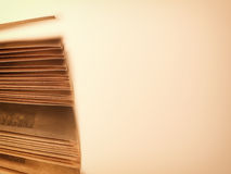 Scattered pages of an open book, on beige Royalty Free Stock Images