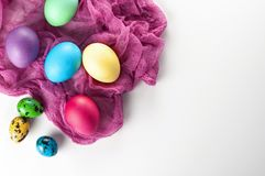 Scattered painted easter chicken and quail eggs on a white backg Royalty Free Stock Image