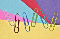 Scattered paper clips on a colorful background. royalty free stock photography