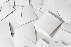Scattered papers. Many scattered small white note papers on a small area Stock Photos