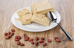 Scattered peanuts, broken peanut halva in white plate, teaspoon. On wooden table Royalty Free Stock Photography