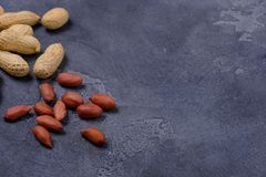 Scattered peanuts on dark stone background Royalty Free Stock Image