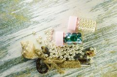 Scattered pearls and old key and jars with pearls and blue beads. Royalty Free Stock Photo