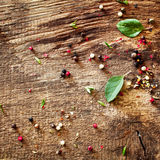 Scattered peppercorns and basil Royalty Free Stock Photo