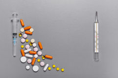 Scattered pills, capsules, thermometer and syringe Stock Photography