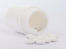 Scattered pills from open white bottle Stock Photo