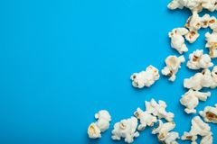 Scattered popcorn on a blue background. Copy space stock photos