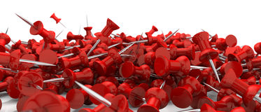 Scattered red pushpins. Falling scattered red pushpins or drawing pins over white surface Stock Photos
