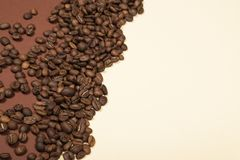 Scattered roasted coffee beans on beige and brown background stock photos