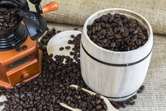 Scattered roasted coffee beans by coffee grinder and wooden barr Royalty Free Stock Photo