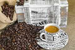 Scattered roasted coffee beans and  espresso coffee beside deliv Stock Image