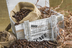 Scattered roasted coffee beans in front of old wooden box with a Royalty Free Stock Images