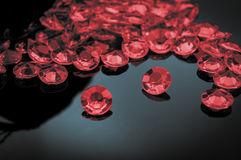 Scattered ruby. Rubies scattered on a shiny surface with prominent ruby in the middle stock photography
