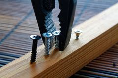 Scattered screws screwed into the wooden plank and pliers. For industrial background Stock Photo