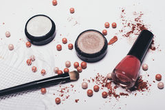 Scattered shadows, applicator, rouge balls and nail polish on a light background. Scattered shadows, applicator, rouge balls and nail polish Royalty Free Stock Images