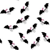 Scattered skulls with pink bow and bat wings. Seamless pattern Stock Images