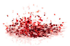 Scattered small red glossy confetti stars fly. On white background Royalty Free Stock Images