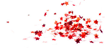 Scattered small red glossy confetti stars fly. On white background Royalty Free Stock Image