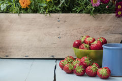 The scattered strawberry fruits in green bowl stock photo