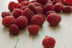 Scattered on the table raspberry. Close-up. Raspberries scattered on the wooden table Stock Photos