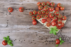 Scattered tomatoes on the wooden table. Stock Photography