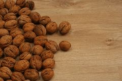 Scattered walnuts on the wooden floor Stock Photos
