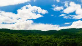 Scattered Clouds Over a Mountain Forest. Scattered white fluffy clouds and a blue sky over a green mountain forest, casting patterns of shadow on top of the royalty free stock images