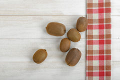 Scattered whole kiwi on a wooden surface with red checkered kitchen tablecloth. Top view Stock Photo