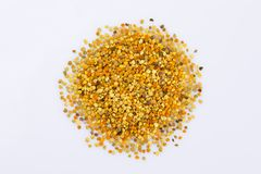 A scattering of bee pollen on a white background. Bright pollen. Bee product. Close-up. Isolated stock photo