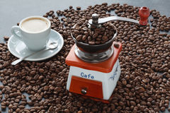 Scattering of coffee beans with hands mill. Scattering of coffee beans with old hands mill Royalty Free Stock Image