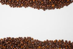 A scattering of coffee beans are located on opposite sides of the photo. The background is white, light, closeup. Direction - cafes, bars,pizzerias Royalty Free Stock Image