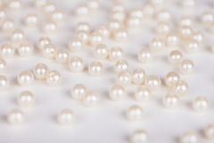 Scattering of fake pearls. On a light surface Stock Photos