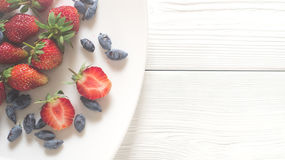 A scattering of fresh berries of strawberry and honeysuckle on a dark wooden boards Royalty Free Stock Photos