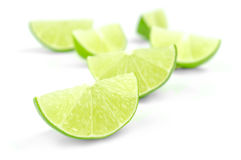 Scattering of fresh lime wedges isolated on a white background.  Royalty Free Stock Image